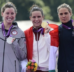 Silver medalist Haley Anderson (USA), gold medalist Eva Risztov (HUN), and bronze medalist Martina Grimaldi (ITA) celebrate on the podium with their medals in the women's open water 10km swimming medals ceremony during the London 2012 Olympic Games at Hyde Park.