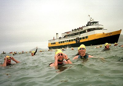 Masters swimmers  at the ALCATRAZ SHARKFEST swim sponsered by Envirosports.   This picture shows swimmers (unknown) as they jump off the boat and swim toward the starting line.