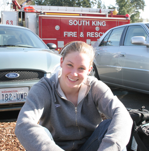Megan Jendrick sitting outside the King County Aquatic Center on the first day of Spring Nationals due to a fire inside the pool.