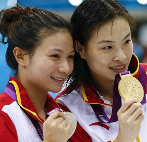 Zi He (CHN), left, and Minxia Wu show off their silver and gold medals respectively for the Women's 3m Springboard final during the London 2012 Olympic Games at Aquatics Centre.