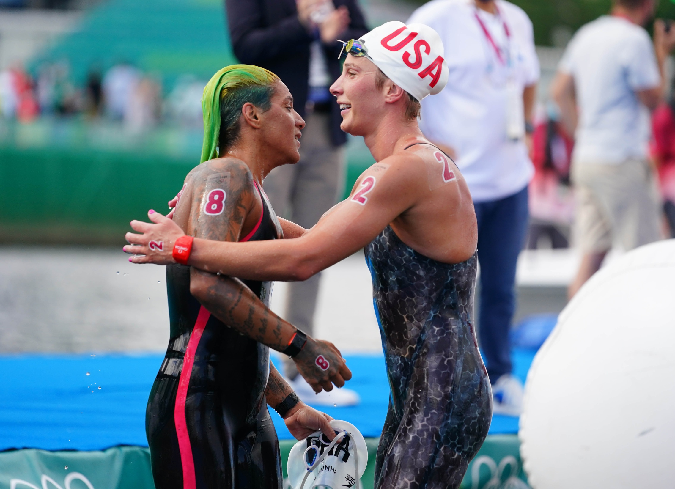 Aug 4, 2021; Tokyo, Japan; Gold medalist Ana Marcela Cunha (BRA) reacts with Ashley Twichell (USA) after winning the women's 10km open water swimming competition during the Tokyo 2020 Olympic Summer Games at Odaiba Marine Park. Mandatory Credit: Kareem Elgazzar-USA TODAY Sports